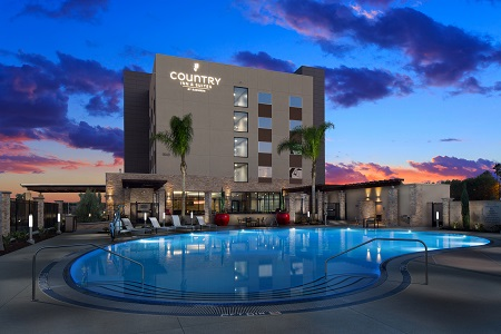 Country Inn & Suites, Anaheim exterior featuring an outdoor pool and sunset views
