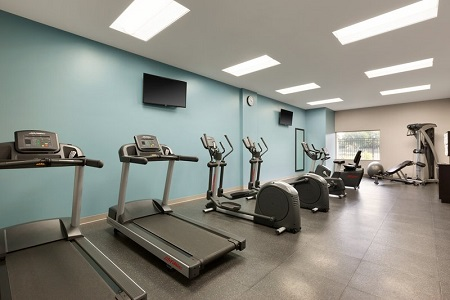 Fitness center with two treadmills, two ellipticals, a multi-gym and a light blue accent wall