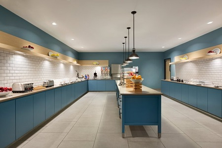 Breakfast servery with blue cabinets, fresh fruit and a make-your-own waffle station
