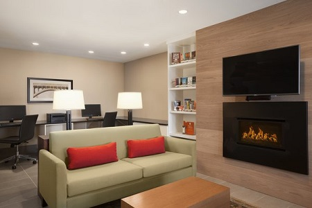 Business center and a green couch with red cushions beside the fireplace