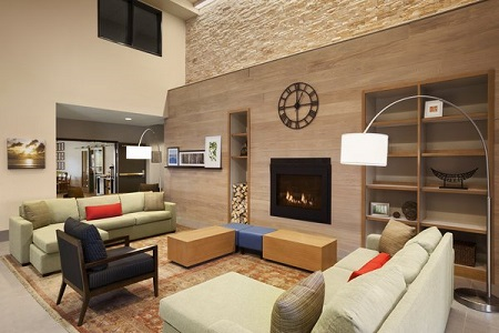 Hotel lobby with modern fireplace, couches and bookshelves