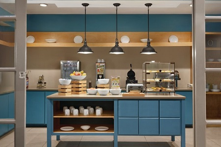 Breakfast room with blue cabinets, fresh fruit and a make-your-own waffle station