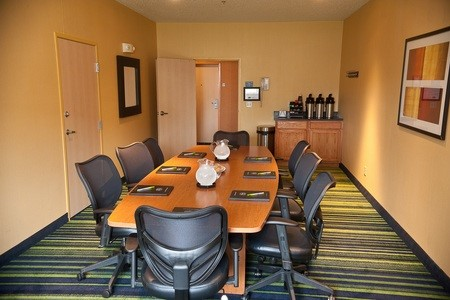 Meeting room with long table, chairs, water pitchers and coffee station
