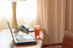 A laptop, phone and glass of iced tea sitting on a work desk