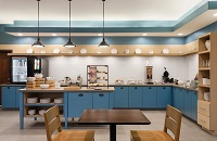 Breakfast room with a dining area, blue cabinets, assorted breads and a make-your-own waffle station