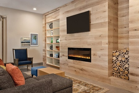 Welcoming lobby with an armchair, a sectional and a flat-screen TV mounted above the fireplace