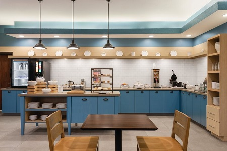 Breakfast servery with a dining area, blue cabinets, assorted breads and a make-your-own waffle station
