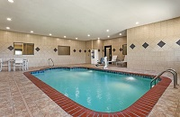 Indoor pool area with beige tiles, white patio furniture and a pool lift