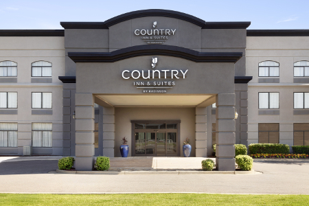 Country Inn & Suites hotel exterior with a large carport and scenic landscaping