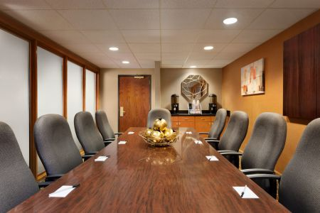 Meeting room with a wooden conference table and comfortable black chairs