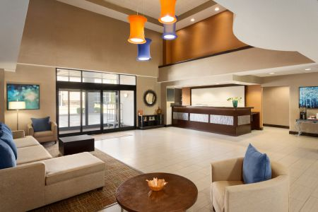 Spacious hotel lobby with modern light fixtures and comfortable beige furniture