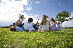 Group of friends sitting together in a grassy field