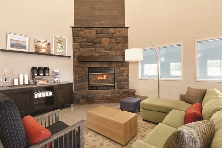 Hotel lobby featuring a coffee station, stone fireplace, green sectional and blue striped armchair