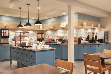 Breakfast area with tables, chairs, blue cabinets, pastries and a make-your-own waffle station