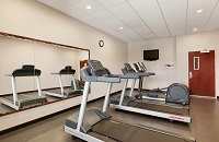 Hotel fitness center with two treadmills, an elliptical and a flat-screen TV