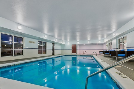 Sparkling indoor pool with blue chairs along the side