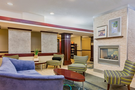 Hotel Lobby With A Purple Sofa And Striped Chairs Around The Fireplace