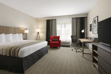Charlottesville Hotel Room With A King Bed And Red Armchair