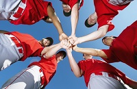 Baseball players wearing red jerseys placing their hands together in a team huddle