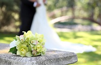 Bouquet with white, pink and yellow flowers on a stone bench in front of a wedding couple