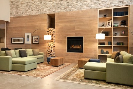 Contemporary lobby with fireplace and green couches