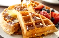 Fresh waffles topped with butter, syrup and fruit