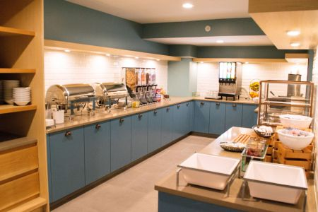 Breakfast room with blue cabinets, assorted cereals and hot entrées