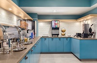 Breakfast room with blue cabinets, assorted cereals and a make-your-own waffle station