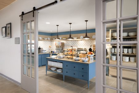 Breakfast servery with blue cabinets, hot meal options and real dinnerware