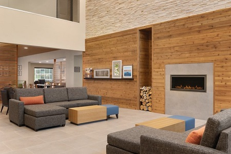 Welcoming lobby with two gray sectionals and a fireplace