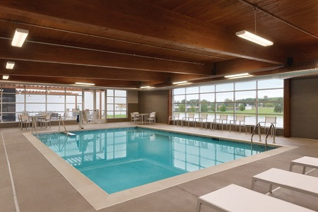 Indoor pool area with large windows and white patio furniture