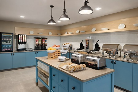 Breakfast servery with fruit, pastries, two waffle irons and blue cabinets