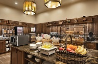 Breakfast room with pastries, bowls of breakfast spreads and a basket full of fresh fruit
