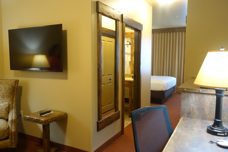 Suite with a king bed, a work desk and a flat-screen TV