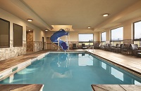 Indoor pool area with lounge chairs and a blue water slide
