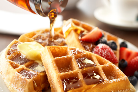 Waffles topped with butter, syrup and fruit