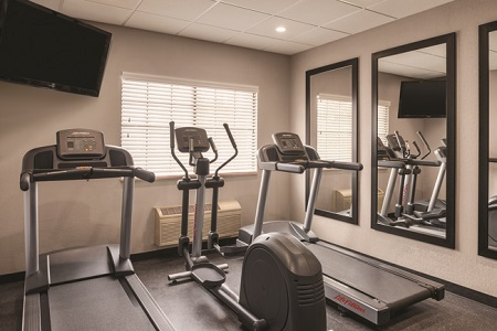 Fitness center with two treadmills, an elliptical and a flat-screen TV