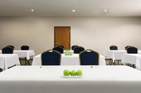 Spacious meeting room with table decor and linens