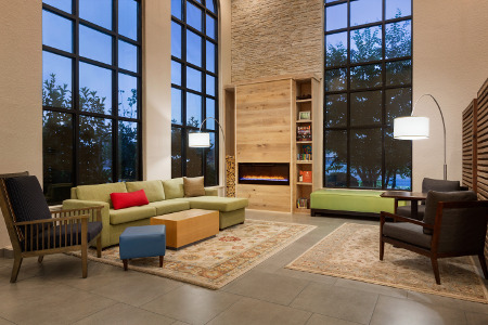 Spacious lobby with fireplace, seating and high ceilings