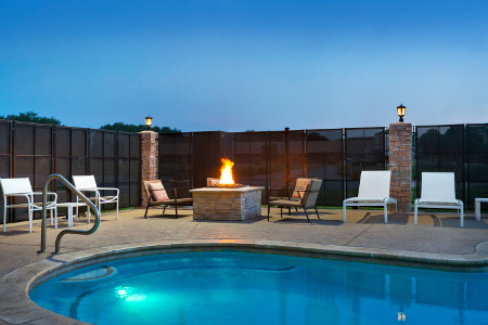 Outdoor pool with lounge chairs and fire pit