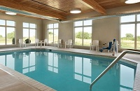 Heated indoor pool surrounded by chairs and large windows