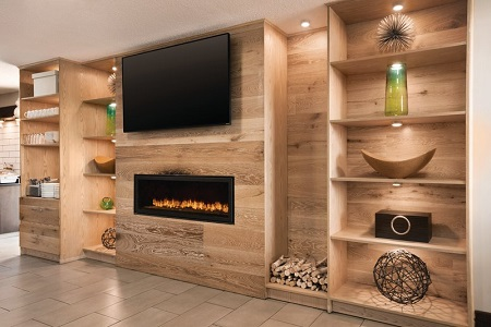 Hotel lobby with bookshelves, a fireplace and a flat-screen TV