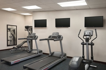 Fitness center with a multi-gym, two treadmills, an elliptical and three mounted TVs