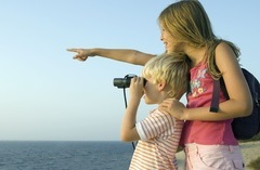 Boy looking through binoculars while his sister points over his shoulder