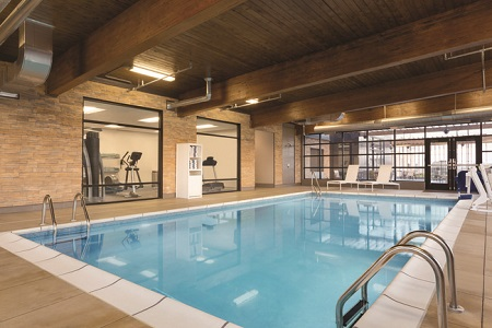 Indoor pool area with white lounge chairs and wooden beams overhead
