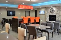 Breakfast area with gray chairs and orange barstools