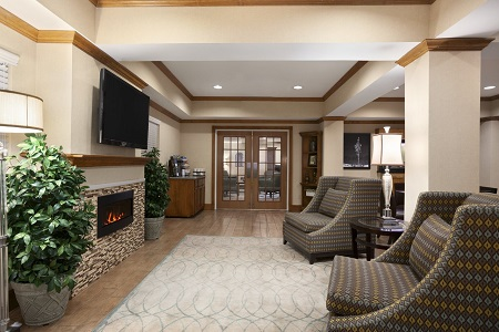Lobby with fireplace, TV and armchairs