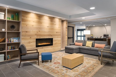 Welcoming lobby with a gray sectional, two armchairs and modern fireplace