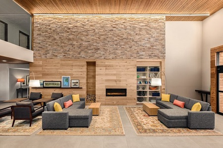 Welcoming hotel lobby featuring two gray sectionals in front of a fireplace