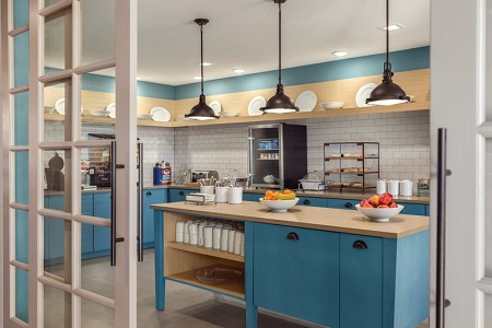 Breakfast servery with blue cabinets, fresh fruit, pastries and a make-your-own waffle station